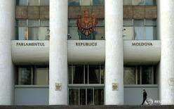 Человек проходит мимо здания парламента Молдавии в Кишиневе 7 марта 2005 года. Новое большинство в парламенте Молдавии после трех месяцев противостояния с президентом утвердило правительство на неожиданно созванном заседании, оставив оппозиции три часа на мобилизацию сторонников, недовольных переходом власти к соратникам магната Владимира Плахотнюка. Bogdan Cristel / Reuters