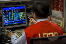 Un operador revisa los precios de diversas cotizaciones bursátiles en el mercado de Hong Kong, China, jul 8, 2015. El índice mundial de acciones de MSCI, que incluye a 46 países, entró el miércoles en lo que el análisis técnico considera un mercado bajista, tras una caída de un 20 por ciento desde el máximo histórico al que llegó en abril de 2015.  REUTERS/Tyrone Siu