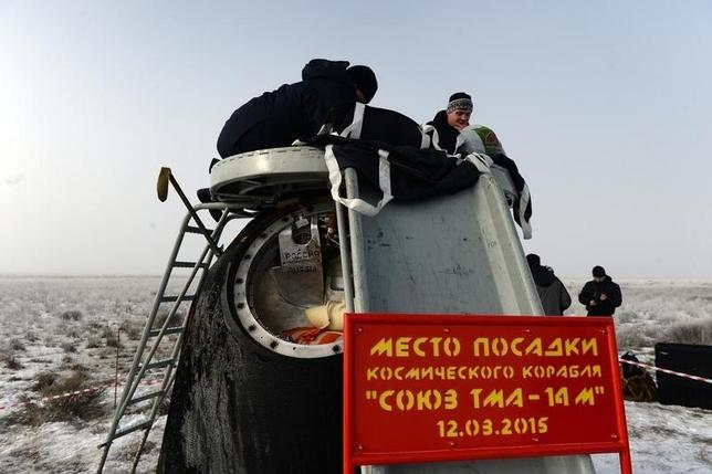 Russia's space agency ground personnel check the Soyuz capsule shortly after it landed in a remote area outside the town of Zhezkazgan in central Kazakhstan,  March 12, 2015.   REUTERS/Vasily Maximov/Pool