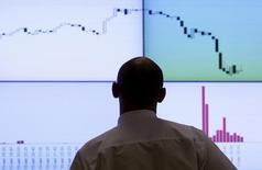 Участник торгов смотрит на экран с фондовыми графиками на бирже РТС в Москве. 11 августа 2011 года. Российский индекс РТС в начала торгов четверга дошел до минимальной отметки с декабря 2014 года на фоне достижения долларом исторического максимума к рублю, но удерживается от дальнейшего снижения. REUTERS/Denis Sinyakov