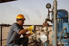 Рабочий на НПЗ Najaf Эн-Наджафе, Ирак 3 октября 2013 года. Ирак экспортирует рекордное количество нефти в январе, несмотря на возвращение Ирана на мировой рынок, и увеличит добычу в этом году, сказал министр нефтяной промышленности Ирака Адель Абдул Махди в интервью Рейтер. REUTERS/Ahmad Mousa