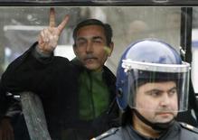 Задержанный в ходе выступлений протеста жестикулирует в полицейском автобусе в Баку 26 января 2013 года. Президент Азербайджана Ильгам Алиев в четверг впервые прокомментировал уличные выступления протеста против падения национальной валюты вслед за нефтью, сообщив, что они были относительно немногочисленными и завершились. REUTERS/David Mdzinarishvili