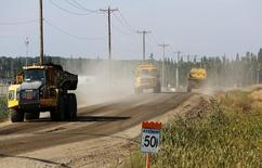 Vehicles transport dirt for building oil infrastructure near the Cenovus Energy Christina Lake Steam-Assisted Gravity Drainage (SAGD) project 120 km (74 miles) south of Fort McMurray, Alberta, August 15, 2013. REUTERS/Todd Korol