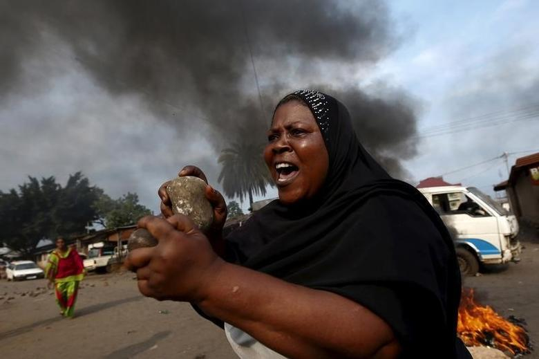 A woman gestures with stones during a protest against President Pierre Nkurunziza and his bid for a third term in Bujumbura, Burundi, May 26, 2015. REUTERS/Goran Tomasevic