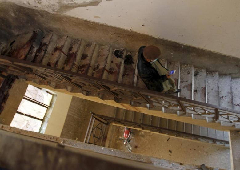 A man walks down the blood-stained stairs leading down from the roof of a dormitory where a militant attack took place, at Bacha Khan University in Charsadda, Pakistan January 20, 2016. REUTERS/Caren Firouz