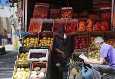 Un vendedor de fruta, sentado en la parte trasera de su camión, espera por clientes junto a un hombre que lee el diario, en una calle de Ciudad de México, 13 de agosto de 2014. El índice de precios al consumidor de México subió un 0.03 por ciento en la primera quincena de enero, dijo el viernes el instituto de estadísticas. REUTERS/Henry Romero