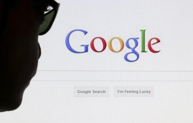A computer user poses in front of a Google search page in this photo illustration taken in Brussels in this May 30, 2014 file photo. REUTERS/Francois Lenoir