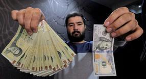 Los bancos internacionales están preparando el restablecimiento de relaciones con la banca iraní empleando el sistema de transferencias SWIFT, dijo el viernes a Reuters el jefe del banco iraní Middle East Bank.  Imagen de un hombre posando con un dólar y la cantidad rials iraníes que le dan al cambio en una casa de cambio en el distrito financiero de Teherán, en Iran, el 20 de enero de 2016. REUTERS/Raheb Homavandi/TIMA