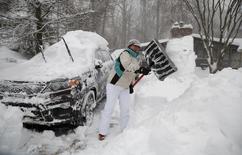 Mulher retirando neve de carro em Falls Curch, Virginia.    23/01/2016    REUTERS/Kevin Lamarque