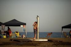 Homem em chuveiro em praia espanhola.    05/07/2015     REUTERS/Jon Nazca