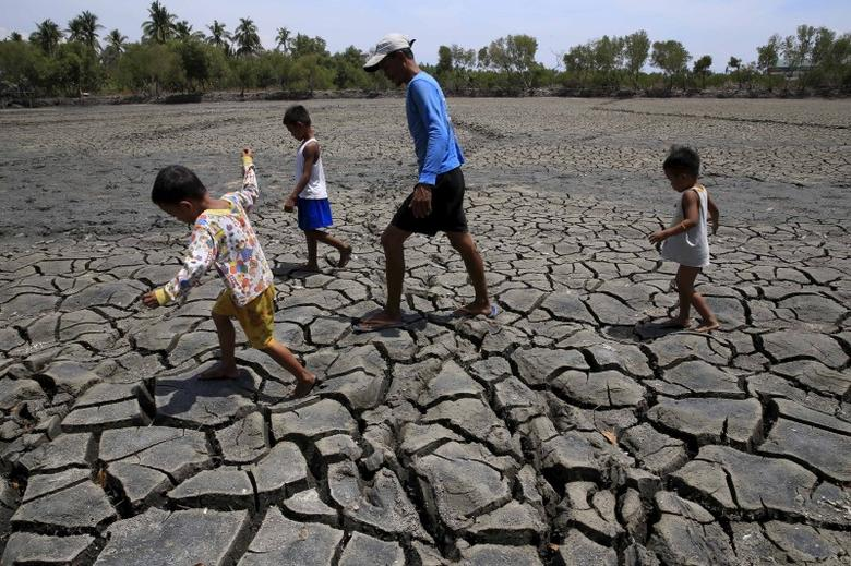 A father with his children walk over the cracked soil of a 1.5 hectare dried up fishery at the Novaleta town in Cavite province, south of Manila May 26, 2015.  REUTERS/Romeo Ranoco