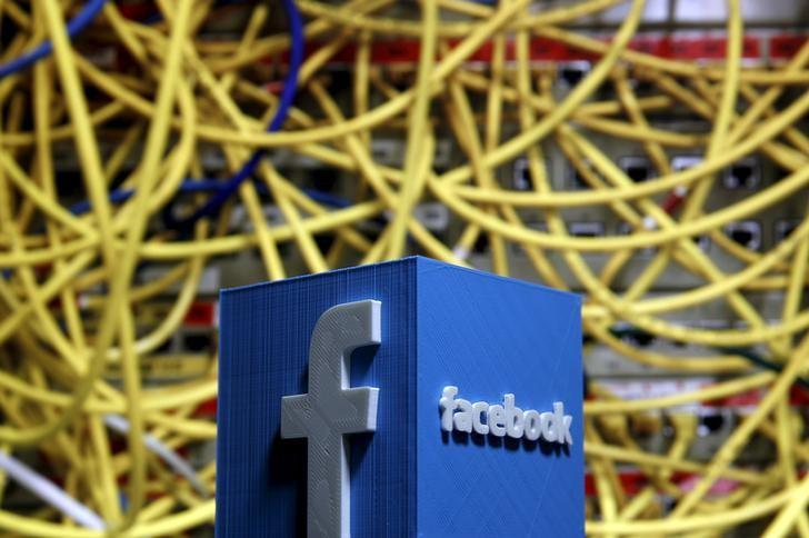 A 3D plastic representation of the Facebook logo is seen in front of displayed cables in this illustration in Zenica, Bosnia and Herzegovina May 13, 2015. REUTERS/Dado Ruvic