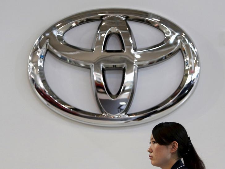 A woman walks under a logo of Toyota Motor Corp at the company's showroom in Tokyo, Japan, August 4, 2015. REUTERS/Yuya Shino