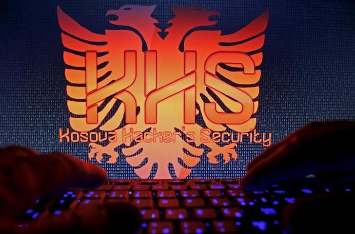 A man types on a keyboard in front of the logo of ''Kosova Hackers Security'' in this photo illustration taken in Sarajevo, Bosnia and Herzegovina, October 16, 2015. REUTERS/Dado Ruvic