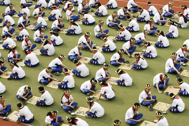 Students play the board game ''Go'', known as ''Weiqi'' in Chinese, during a competition to mark the 100-day countdown to the opening of Beijing Olympics at a primary school in Suzhou, Jiangsu province, in this April 30, 2008 file photo.  REUTERS/China Daily/Files