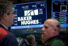 Operadores en el puesto de Baker Hughes en la bolsa de Wall Street en Nueva York, nov 17, 2014. El proveedor de servicios para yacimientos petroleros Baker Hughes Inc, que está siendo comprado por su rival Halliburton Inc, prevé que la cifra global de pozos petroleros caiga en hasta un 30 por ciento en el 2016, dado que el desplome de los precios del crudo no da señales de detenerse.  REUTERS/Brendan McDermid
