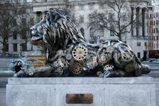 A pedestrian photographs a lion sculpture installed by National Geographic Wild to highlight the threat to endangered big cats, in Trafalgar Square in London, January 28, 2016.   REUTERS/Stefan Wermuth