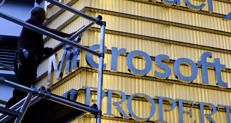 A worker cleans the letters of a Microsoft sign outside a corporate office in New York City, in this July 29, 2015 file photo. REUTERS/Rickey Rogers/Files