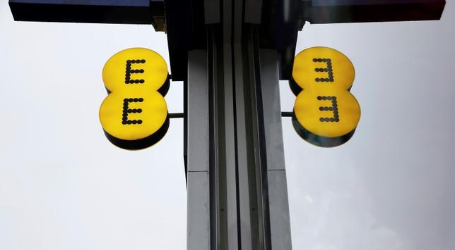 The EE logo is reflected in a window outside an EE shop in London, in this file photograph dated February 5, 2015.  REUTERS/Suzanne Plunkett/files