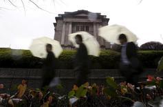 Прохожие у здания Банка Японии в Токио. 29 января 2016 года. Банк Японии неожиданно установил ключевую ставку на уровне -0,1 процента в пятницу, шокировав инвесторов очередным смелым манёвром, направленным на оживление экономики страны в условиях рыночной волатильности и замедления глобального роста. REUTERS/Yuya Shino