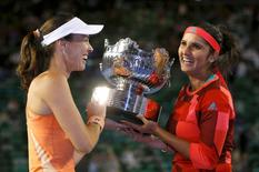 Switzerland's Martina Hingis (L) and India's Sania Mirza pose with the trophy after winning their doubles final match at the Australian Open tennis tournament at Melbourne Park, Australia, January 29, 2016. REUTERS/Issei Kato