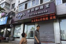 A boy looks up as he walks past the closed coffee shop owned by Canadian couple Kevin Garratt and Julia Dawn Garratt in Dandong, Liaoning province, August 5, 2014. REUTERS/Ben Blanchard