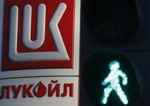 A green traffic light signal is seen in front of a Lukoil petrol station in St. Petersburg November 26, 2013. Lukoil, Russia's No.2 oil producer, posted $7.8 billion in net profit in 2013, missing forecasts and down from $11 billion in the previous year. Picture taken November 26, 2013. REUTERS/Alexander Demianchuk/Files (RUSSIA - Tags: ENERGY BUSINESS)