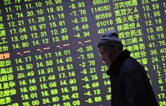 El Ibex-35 cerró al alza el viernes, pero no pudo evitar firmar su peor mes de enero en seis años con un descenso acumulado de casi el ocho por ciento afectado por la persistente caída del precio del petróleo y las dudas sobre la fortaleza de la economía china. En la imagen, un inversor pasa por delante de una pantalla electrónica con información sobre precios bursátiles en una casa de valores en Hangzhou, provincia de Zhejiang, 21 de enero de 2015. REUTERS/China Daily
