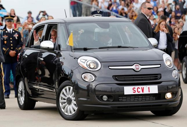 Pope Francis waves as he is driven away in a Fiat 500 model after arriving in the United States at Joint Base Andrews outside Washington in this September 22, 2015 file photo.   REUTERS/Jonathan Ernst/Files
