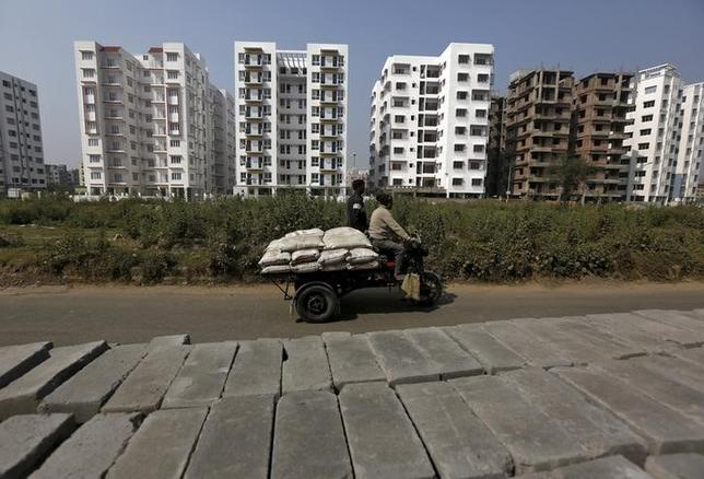Labourers transport cement bags onto an improvised motorised rickshaw at the construction site of a residential complex on the outskirts of Kolkata, India January 23, 2016. REUTERS/Rupak De Chowdhuri