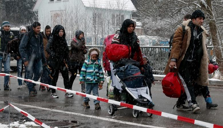 Migrants stay in queue during heavy snowfall before passing Austrian-German border in Wegscheid in Austria, near Passau November 22, 2015. REUTERS/Michael Dalder