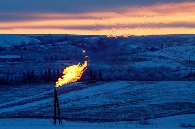 A natural gas flare on an oil well pad burns as the sun sets outside Watford City, North Dakota January 21, 2016. REUTERS/Andrew Cullen/Files