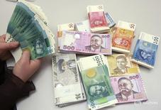 Сотрудник Нацбанка Киргизии считает деньги. Бишкек, 19 февраля 2010 года. Правительство Киргизии приняло решение конвертировать часть ипотечных кредитов в долларах в сомы после почти 30-процентной девальвации национальной валюты, возьмет риски на себя. REUTERS/Vladimir Pirogov