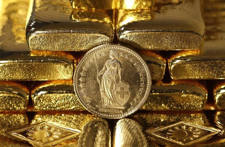 Gold bars and a Swiss Franc coin are seen in this illustration picture taken at the Austrian Gold and Silver Separating Plant 'Oegussa' in Vienna November 7, 2014.  REUTERS/Leonhard Foeger/Files