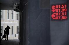 Электронное табло в Москве, демонстрирующее курсы доллара и евро к рублю.  Рубль начал торги вторника потерей более процента стоимости на фоне текущего снижения нефти и возможного сокращения продаж экспортной валютной выручки после уплаты январских налогов; внутридневная динамика останется в зависимости от нефтяных котировок. REUTERS/Maxim Zmeyev