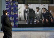 Un hombre mira un tablero electrónico con información bursátil, afuera de una correduría en Tokio, Japón. 20 de enero de 2016. Las bolsas de Asia caían el martes luego de que los precios del crudo retrocedieron por el temor sobre el exceso de la oferta y de que datos pesimistas de manufactura avivaron la inquietud sobre un crecimiento económico global débil. REUTERS/Toru Hanai