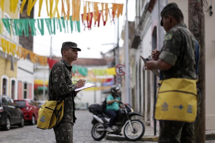 Brazilian soldiers conduct an inspection for the Aedes aegypti mosquito on a street in Recife, Brazil, February 1, 2016. REUTERS/Ueslei Marcelino
