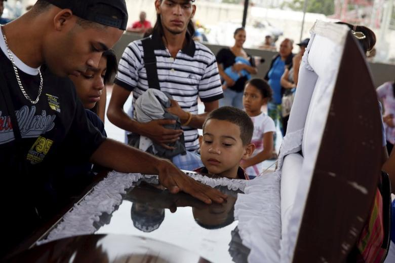 A boy looks inside the coffin of a crime victim, during a tribute prior to his burial in Caracas November 25, 2015.   REUTERS/Carlos Garcia Rawlins