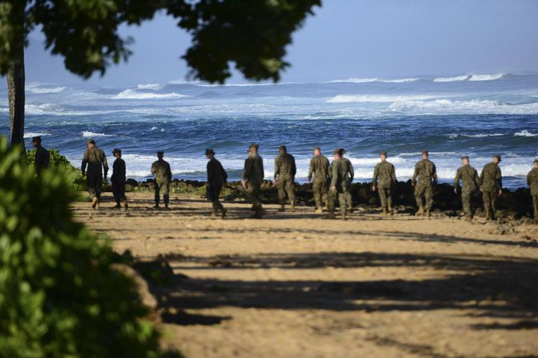 A group of Marines walk the beach outside the Haleiwa Incident Command Post in Haleiwa, Hawaii, during search efforts for 12 missing Marines, in this handout photo taken January 18, 2016.  REUTERS/U.S. Coast Guard/Petty Officer 1st Class Levi Read/Handout via Reuters