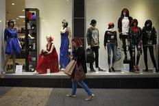 Las ventas minoristas de la zona euro subieron en diciembre sobre todo gracias a las compras navideñas de comida, bebida y tabaco, dijo el miércoles la oficina de estadística de la Unión Europea. En la imagen, una mujer sujetando bolsas de compra mira su móvil pasando por delante de un escaparate de ropa en Malaga, España, el 27 de noviembre de 2015. REUTERS/Jon Nazca - RTX1W6RV
