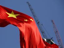 La bandera nacional de China delante de grúas en un distrito comercial en Pekín, China, 26 de enero de 2016. China estableció una proyección de crecimiento de entre 6,5 y 7 por ciento para este año, pero los esfuerzos para reducir el exceso de capacidad podrían aumentar el desempleo en algunas provincias, dijo el miércoles un funcionario del máximo organismo de planificación económica del país. REUTERS/Kim Kyung-Hoon