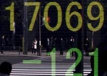 Peatones se reflejan en un tablero electrónico que muestra el índice Nikkei, afuera de una correduría en Tokio, Japón, 4 de febrero de 2016. El índice Nikkei de la bolsa de Tokio cayó el jueves a un mínimo en una semana luego de la fortaleza del yen debilitó la confianza de los inversores, mientras que las acciones de empresas como Panasonic Corp y Hitachi Ltd se desplomaron debido a un recorte en sus previsiones de ganancias. REUTERS/Yuya Shino