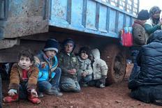 """Вынужденные покинуть свои дома дети, бежавшие вместе с родителями от насилия в контролируемых """"Исламским государством"""" районах Сирии, сидят под грузовиком в селении Акда в ожидания перехода границы в направлении Турции. Фото от 23 января 2016. Наступление сирийской армии в пригородах Алеппо заставило покинуть дома минимум 15.000 человек и в январе сопровождалось 13-ю авиаударами по медицинским учреждениям, сообщила в пятницу ООН. REUTERS/Abdalrhman Ismail"""