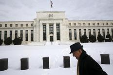 A man walks past the snow-covered grounds of the U.S. Federal Reserve in Washington January 26, 2016. REUTERS/Jonathan Ernst