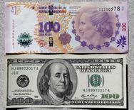 Foto de archivo de un billete de 100 pesos argentinos mostrado junto a un billete de 100 dólares estadounidenses, en Buenos Aires. 17 de septiembre de 2014. El dólar en el mercado cambiario informal cotizaba el viernes sorpresivamente por debajo del cambio oficial, ya que la abundancia de divisas hacía perder a los inversores el interés que tenían en un activo que fue clave en sus carteras hasta el año pasado. REUTERS/Enrique Marcarian/Files