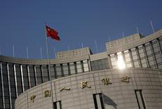 En la imagen, la bandera china ondea sobre la sede del banco central chino en Pekin el 19 de enero de 2016. China ajustará la política monetaria y mantendrá al yuan básicamente estable mientras que seguirá vigilando los riesgos financieros sistémicos, dijo el sábado el banco central del país en un informe del cuarto trimestre. REUTERS/Kim Kyung-Hoon