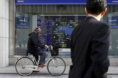 Un hombre en bicicleta pasa delante de un tablero electrónico que muestra la información de los índices de mercado de varios países, afuera de una correduría en Tokio, Japón, 4 de febrero de 2016. Las bolsas de Asia reducían pérdidas el lunes luego de que un yen depreciado ayudó al índice Nikkei de Japón a cortar una racha de cuatro días de caídas, pero el volumen de negocios era débil en momentos en que muchos mercados regionales están cerrados por el período festivo del Año Nuevo Lunar. REUTERS/Yuya Shino