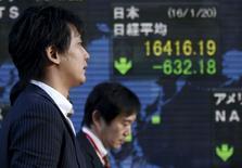 Un hombre camina junto a un tablero electrónico que muestra el índice Nikkei, afuera de una correduría en Tokio, Japón. 20 de enero de 2016. El índice Nikkei de la bolsa de Tokio rebotó el lunes en una sesión volátil, cortando una racha de cuatro días de pérdidas, luego de que la debilidad del yen contrarrestó las preocupaciones sobre las débiles ganancias de las compañías japonesas y una caída de las acciones en Estados Unidos. REUTERS/Toru Hanai