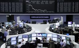 Traders work at their desks in front of the German share price index, DAX board, at the stock exchange in Frankfurt, Germany, February 8, 2016.     REUTERS/Staff/Remote