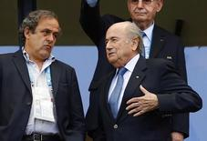FIFA President Sepp Blatter speaks with UEFA President Michel Platini (L) before the 2014 World Cup Group G soccer match between Germany and Portugal at the Fonte Nova arena in Salvador June 16, 2014.      REUTERS/Darren Staples